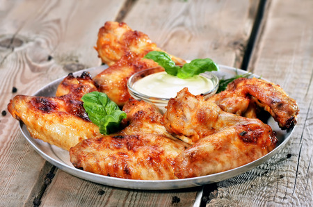 Baked chicken wings with sauce on wooden table, close up view