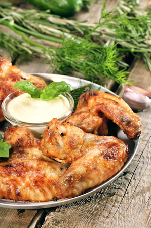Fried chicken wings with sauce on wooden table photo