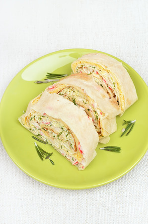 Lavash rolls with crab meat, cheese, eggs and herbs on green plate, top view photo