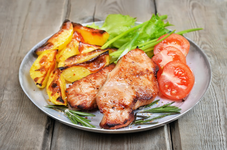 Grilled pork chop with baked potatoes and fresh vegetables on rustic table photo
