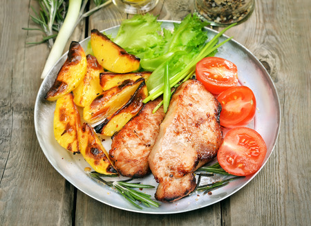 baked potatoes: Grilled steak with baked potatoes and fresh vegetables on rustic table