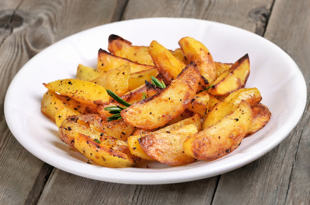 Potato wedges on white plate, fast food, close up view