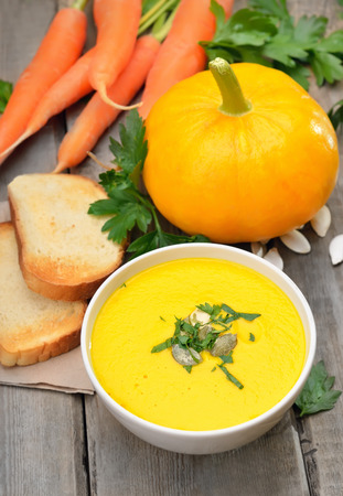 Pumpkin soup, raw pumpkin, carrots and toasted bread on rustic wooden table photo