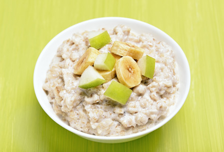 Porridge oats with apple and bananas slices in white bowl on green table