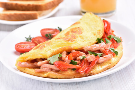 breakfast plate: Egg omelette with vegetables and ham on white plate, close up view