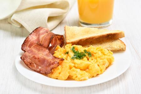 El desayuno con huevos revueltos y tocino en la placa blanca Foto de archivo