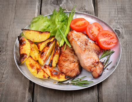 baked potatoes: Grilled pork chop with baked potatoes and fresh vegetables on rustic table