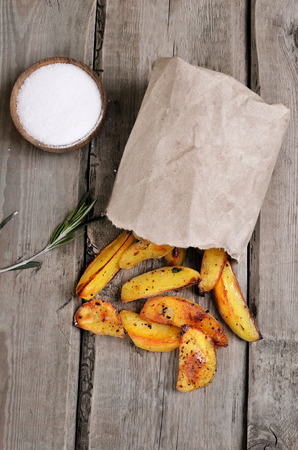 Baked potato wedges in paper bag on rustic table Stock Photo