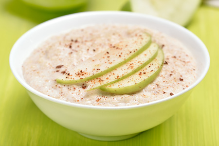 Oatmeal porridge with apple slices and cinnamon in white bowl Standard-Bild