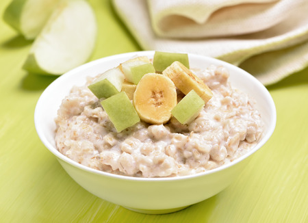 Oatmeal porridge with apple and bananas slices in white bowl on green table Stock Photo