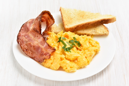 Scrambled eggs with bacon and toasts on white plate, close up view Stock Photo