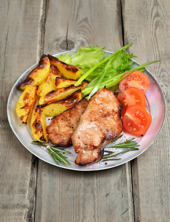 baked potatoes: Roasted pork chop with baked potatoes and fresh vegetables on rustic table