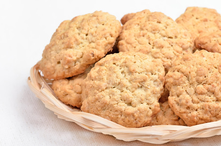 Oatmeal cookies in wicker bowl on white background photo