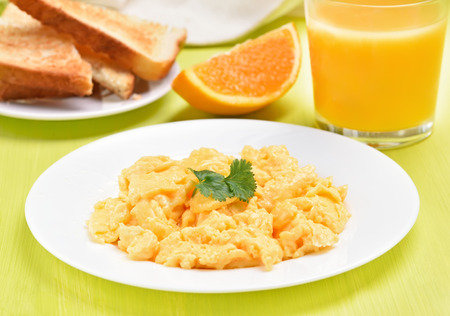 Breakfast scrambled eggs on white plate, toast and orange juice Stock Photo