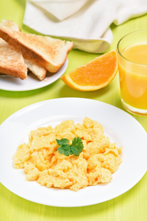 Morning food - scrambled eggs on white plate, toast and orange juice