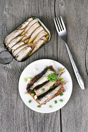 wooden table top view: Sprats sandwich on wooden table, top view