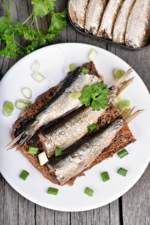 sprats: Sandwich with sprats on wooden table, close up, top view