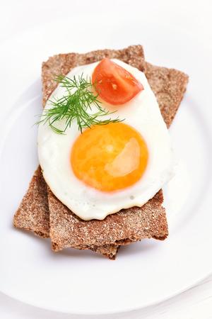 tomato slice: Fried egg, dill and tomato slice on crispbread, top view Stock Photo