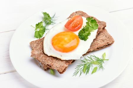 tomato slice: Crispbread with egg, tomato slice and herbs, close up view