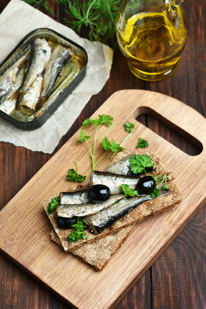 sprats: Crispbread with sprats and olives on wooden cutting board Stock Photo
