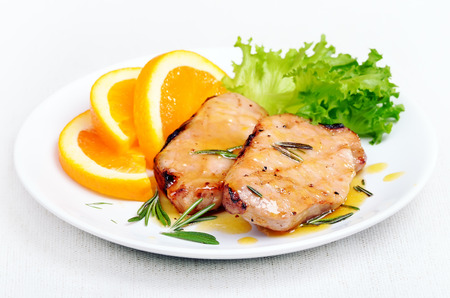 Delicious pork chop with orange sauce and herbs on white plate Stock Photo