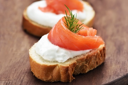 Appetizer with salmon on wood, close up view