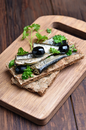 sprats: Fish sprats sandwich on wooden cutting board Stock Photo