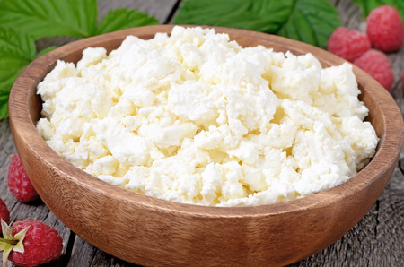 close up view: Fresh curd cheese in wooden bowl, close up view