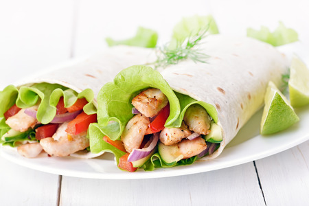 Tortilla wraps with chicken meat and fresh vegetables on white plate