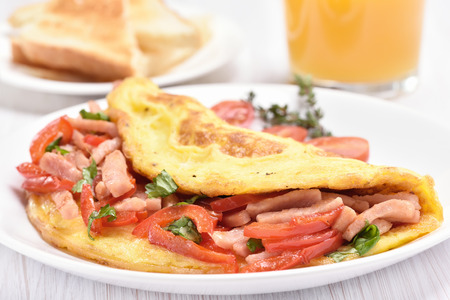 Omelette with vegetables and ham on white plate, close up view photo