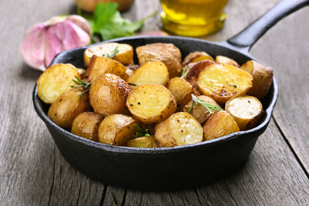 Baked potato in frying pan, close up view Stock Photo