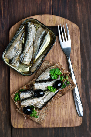 sprats: Sprats on wooden cutting board, top view