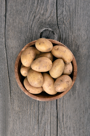 Raw potatoes in bowl on wooden table, top view Stock Photo