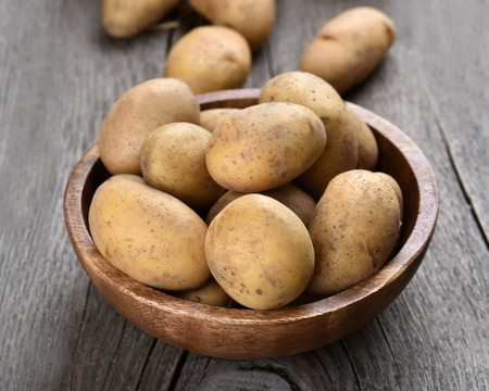 Raw potatoes in bowl on wooden background, close up view
