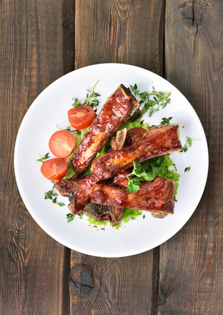 salad plate: Roasted pork ribs on white plate over wooden table, top view Stock Photo