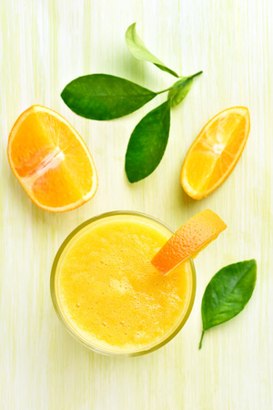 orange yellow: Orange smoothie in glass, top view
