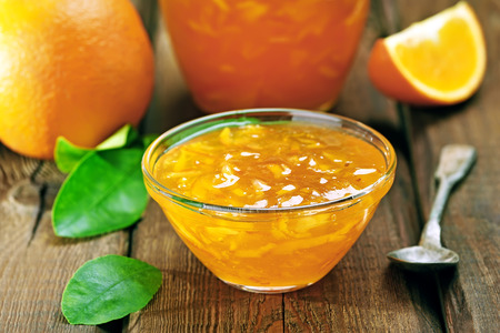 mermelada: Mermelada de naranja en la mesa de madera, se centran en el atasco en un taz�n, profundidad de campo