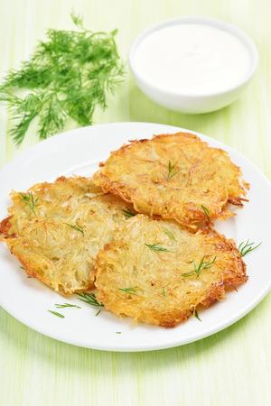 sour cream: Fried potato pancakes, sour cream and dill Stock Photo