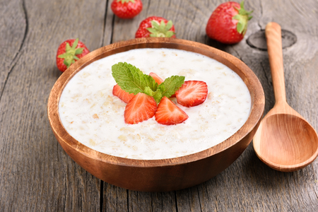 grits: Tasty oatmeal with strawberry slices in bowl on rustic table Stock Photo