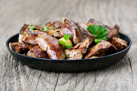 meat dish: Chicken liver in frying pan on wooden table