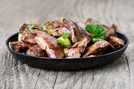 higado de pollo: H�gado de pollo en la sart�n sobre la mesa de madera