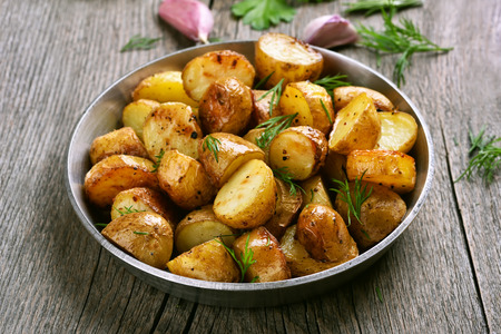 Baked potato in pan on wooden table Stock Photo - 44870614