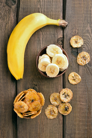Fresh bananas and chips on wooden table, top view. Focus on fresh slices bananas