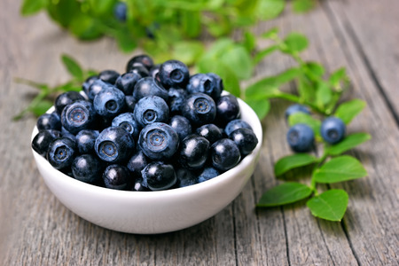 Bowl of blueberries in white bowl on wooden table