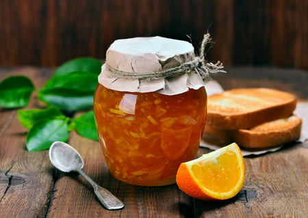 Orange jam in glass jar and slices on wooden table Stockfoto