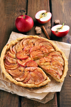Apple pie with cinnamon on wooden table