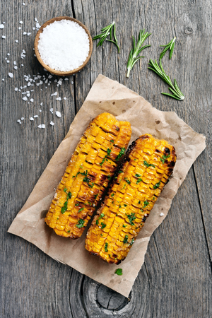 cob: Grilled corn cobs on wooden background, top view
