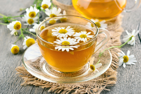 daisy flower: Herbal chamomile tea in glass cup on wooden table Stock Photo