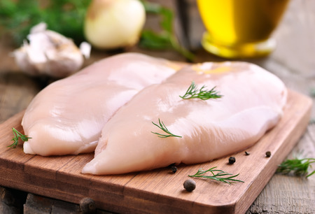 seni: petti di pollo crudo e spezie su tagliere di legno, vista da vicino