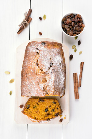 wooden table top view: Pumpkin bread and ingredients on white wooden table, top view